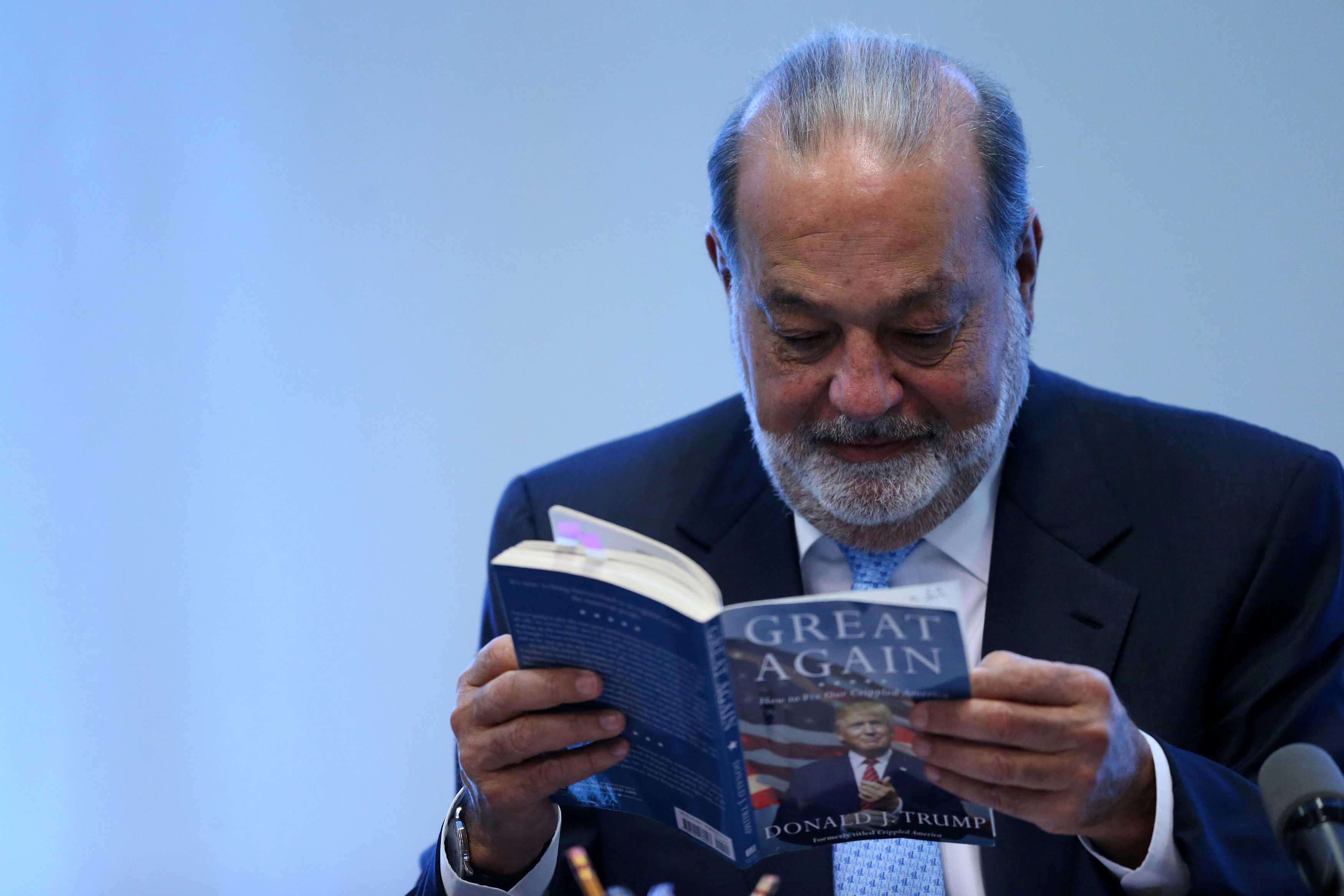 Carlos Slim lee el libro de Donald Trump, en conferencia en la Ciudad de México. Foto de Reuters