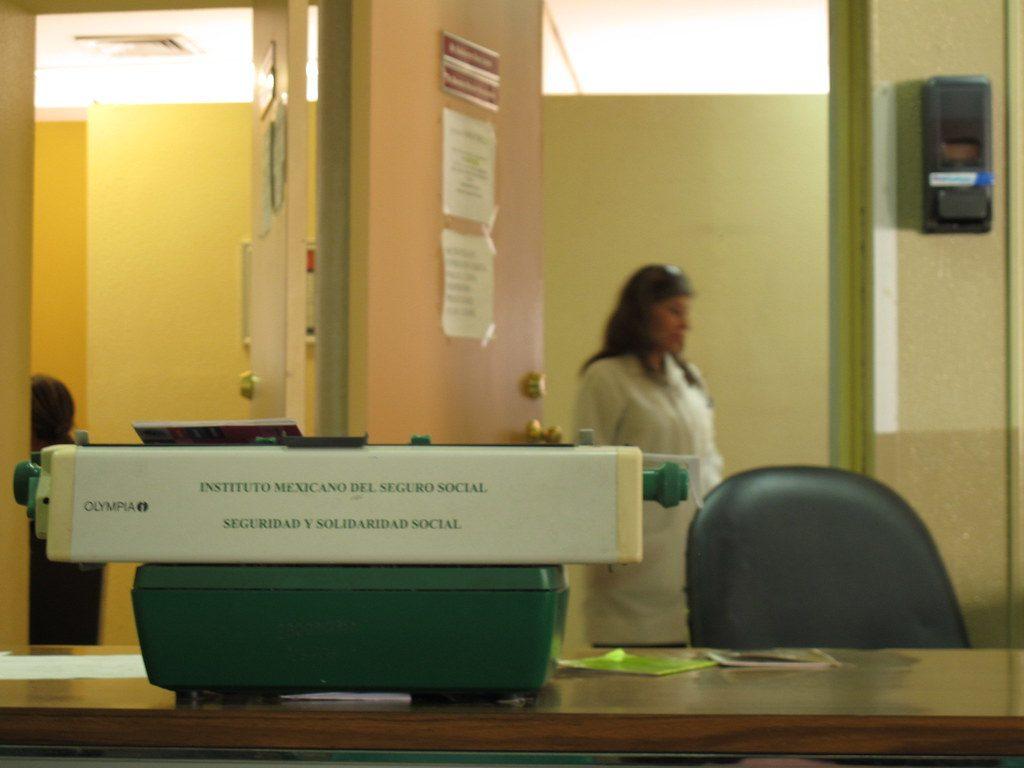 """""""Sabes que el país no funciona, pero nunca te dan más ganas de llorar que cuando recién salido de una cirugía te tienes que chutar 4 horas esperando por una incapacidad (y de un procedimiento que ellos no realizaron)"""", escribió Karina Villalobos para acompañar esta foto del IMSS de 2010, que tiene en primer plano una máquina de escribir Olympia, fuera de catálogo. Foto: Karina Villalobos / Flickr / Licencia CC BY-NC-SA 2.0"""